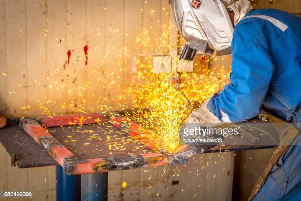 Worker wearing safety gear using grinder with sparks flying