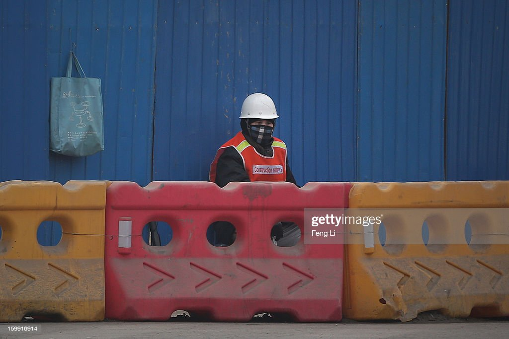A worker wearing the mask sits outside the construction site during severe pollution on January 23, 2013 in Beijing, China. The air quality in Beijing on Wednesday hit serious levels again, as smog blanketed the city.