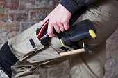 Worker wearing work pants with tools in pockets
