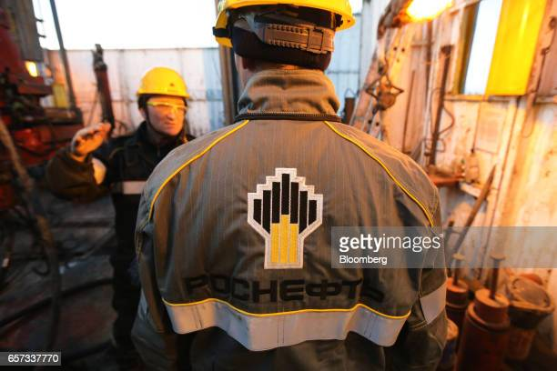 A worker wears a branded safety jacket while working on a drilling rig operated by Rosneft PJSC in the Samotlor oilfield near Nizhnevartovsk Russia...