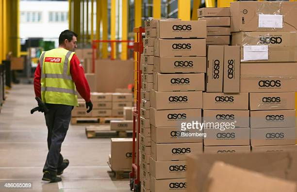A worker wears a Norbert Dentressangle SA branded HiVis safety jacket as he passes boxes of completed orders at Asos Plc's distribution warehouse in...