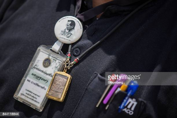 A worker wears a pin featuring a picture of King Bhumibol Adulyadej while preparing the ceremonial ground for Bhumibol's cremation at Sanam Luang...