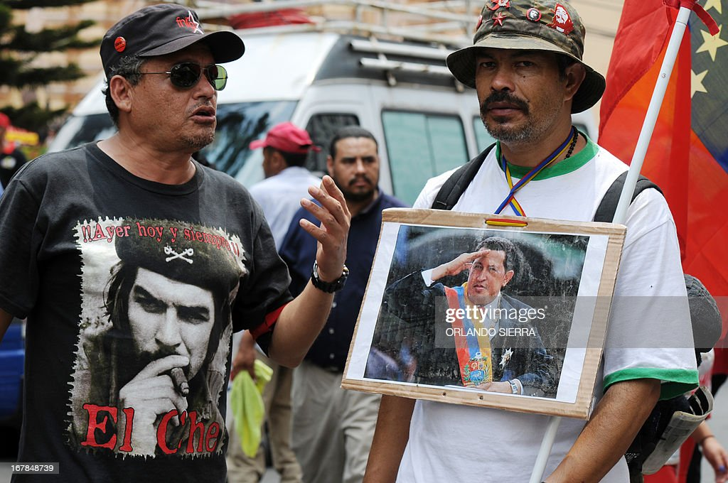 A worker wears a t-shirt with a portrait of Argentine born guerrilla leader Ernesto Che Guevara (L) as another shows a picture with Venezuelan late president Hugo Chavez during May Day celebrations in Tegucigalpa on May 1, 2013. AFP PHOTO / Orlando SIERRA