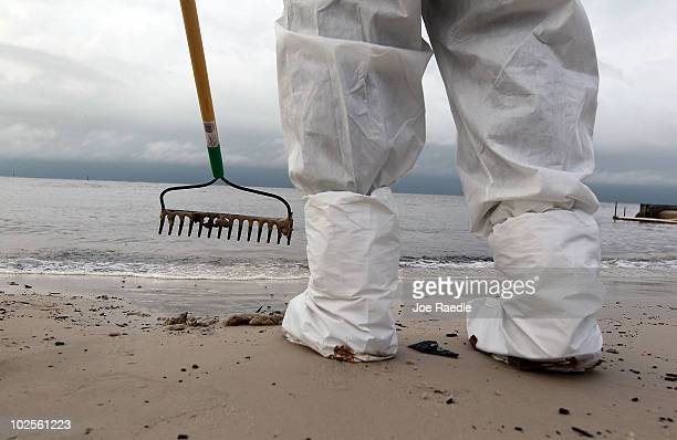 A worker wears protective gear as he uses a rake to collect oil globs that were washing ashore from the Deepwater Horizon oil spill in the Gulf of...