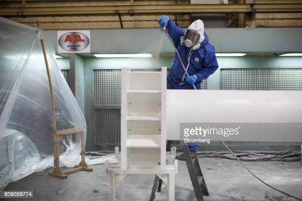 A worker wears protective gear while powder coating a pole at the Automatic Coating Ltd facility in Toronto Ontario Canada on Wednesday Jan 11 2017...