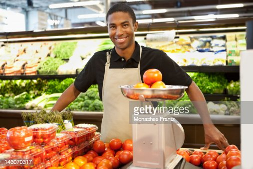 Worker weighing fruit in supermarket : Photo
