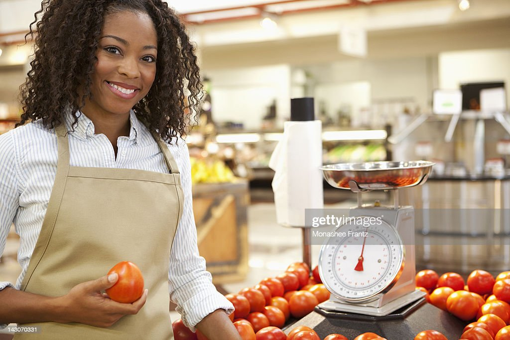 Worker weighing produce in supermarket : Stock Photo