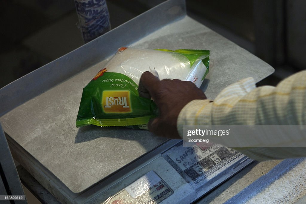 A worker weighs one-kilogram sugar packets in the packaging unit of the Simbhaoli Sugars Ltd. mill in Ghaziabad, Uttar Pradesh, India, on Tuesday, Feb. 26, 2013. India, the world's biggest sugar producer, plans to seek a consensus among various ministries on ending four-decade old state controls on the domestic industry, Food Minister K.V. Thomas said. Photographer: Prashanth Vishwanathan/Bloomberg via Getty Images