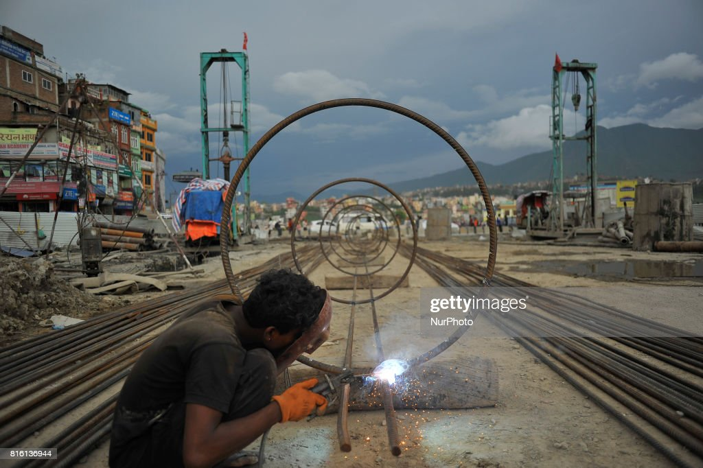A Worker welding iron pillar for on-going Bridge expansion work supported by China AID at Kalanki, Kathmandu, Nepal on Monday, July 17, 2017. The workers used to earn daily wage of NRs. 800 (US$ 8) per day.