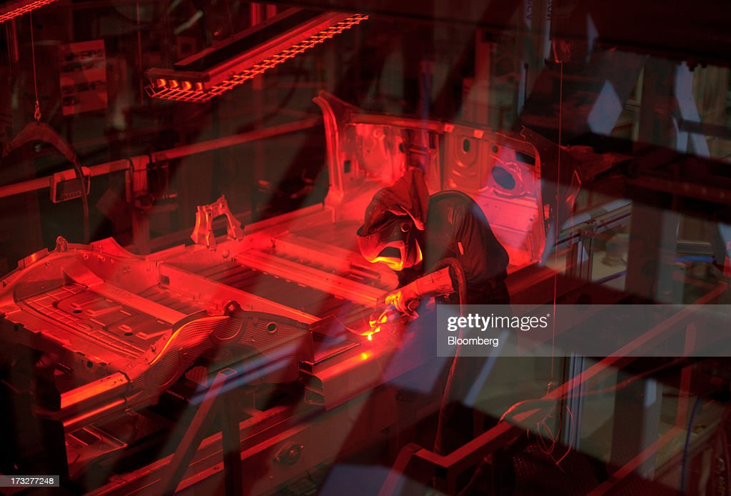 A worker welds a Model S sedan chassis at Telsa Motor Inc.'s assembly plant in Fremont, California, U.S., on Wednesday, July 10, 2013. Tesla is building Model S electric sedans faster than its initial 400-a-week goal as demand and the companys production skills increase, Chief Executive Officer Elon Musk said. Photographer: Noah Berger/Bloomberg via Getty Images