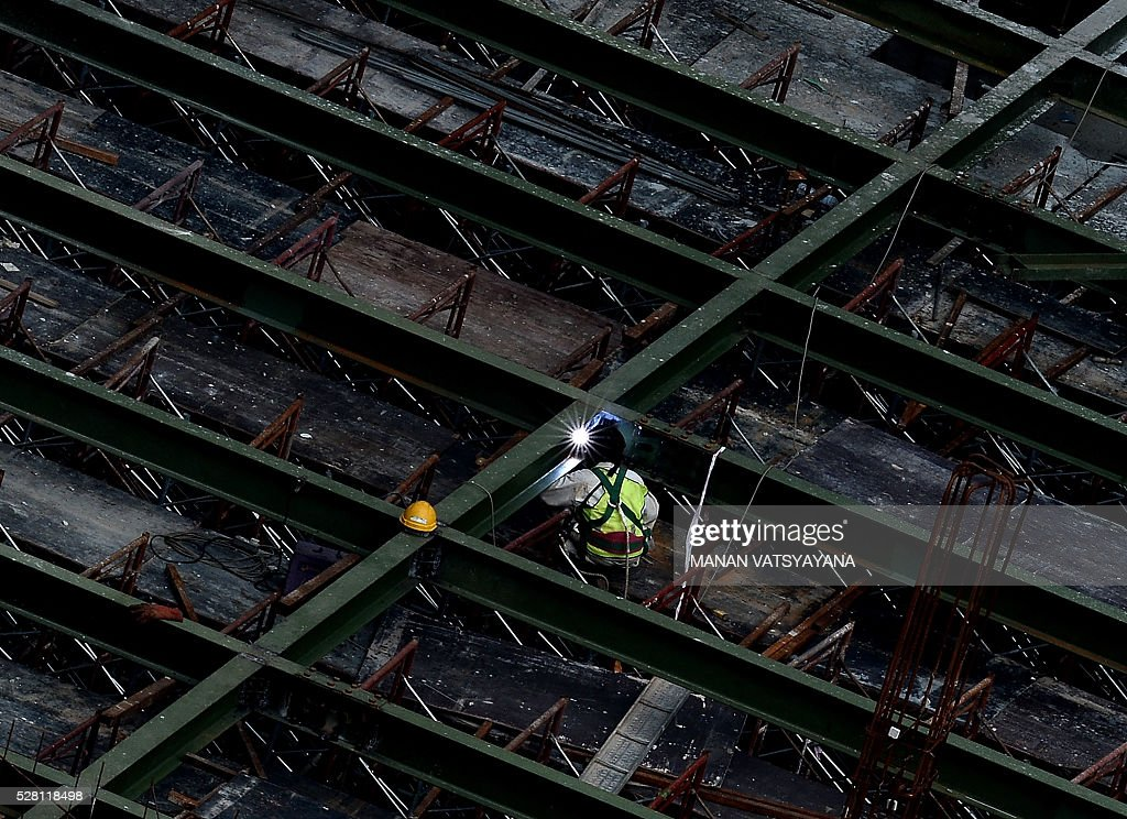 A worker welds iron bars at an under-construction site in Kuala Lumpur on May 4, 2016. / AFP / MANAN