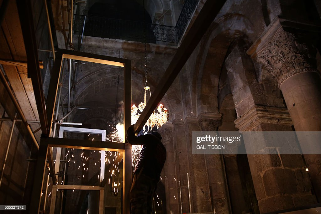 A worker welds scaffoldings at the Church of the Holy Sepulchre in Jerusalem's Old City ahead of the restoration of the Tomb of Jesus on May 29, 2016. The tomb where Jesus is said to have been buried before his resurrection, is to undergo major restoration. The restoration entrusted to a Greek team, is expected to be completed in early 2017 and the site will remain open to visitors in the meantime. / AFP / GALI