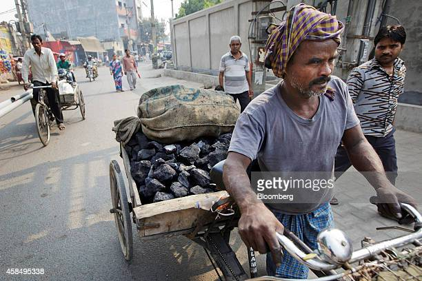 A worker wheels a bicycle trailer laden with coal through a street in New Delhi India on Wednesday Nov 5 2014 Prime Minister Narendra Modi is seeking...