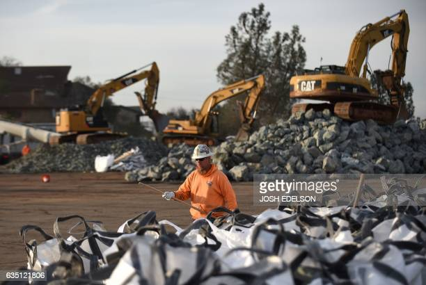 A worker who declined to give his name works with bags of rocks in preparation for emergency measures taken at the Oroville Dam in Oroville...
