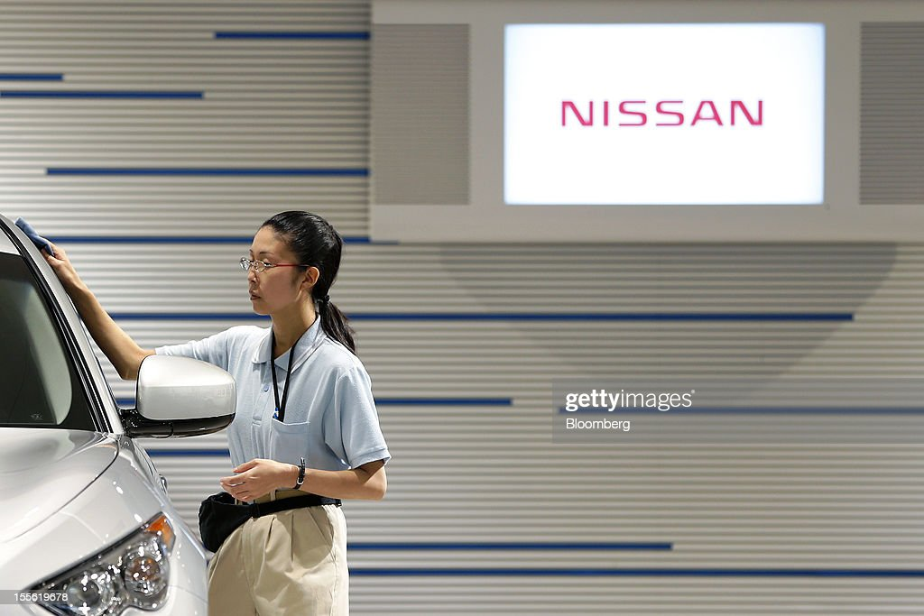 A worker wipes a Nissan Motor Co. vehicle displayed at the company's headquarters in Yokohama City, Kanagawa Prefecture, Japan, on Tuesday, Nov. 6, 2012. Nissan, the top Japanese seller of vehicles in China, cut its full-year net income forecast 20 percent after consumer backlash stemming from a territorial dispute sent sales lower in its largest market. Photographer: Kiyoshi Ota/Bloomberg via Getty Images