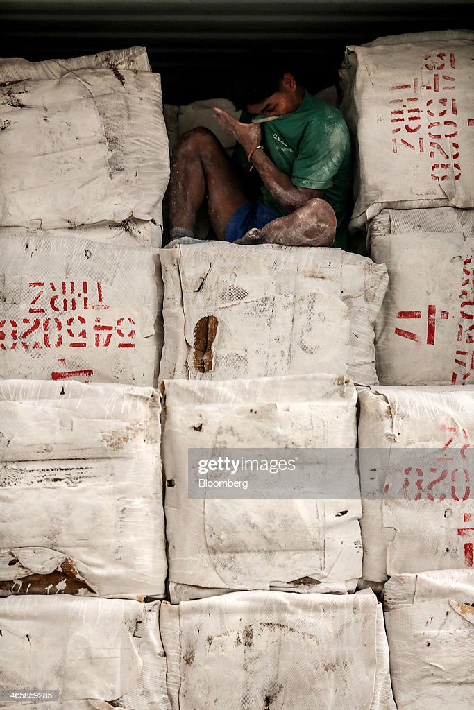 A worker wipes his face while loading bundles of smoked rubber sheets onto a truck for shipment at the Thai Hua Rubber Pcl factory in Samnuktong, Rayong province, Thailand, on Wednesday, Jan. 29, 2014. Rubber production in Thailand, the world's largest exporter, may decline as growers from the main producing regions join protests seeking to overthrow the government, according to Von Bundit Co. Photographer: Dario Pignatelli/Bloomberg via Getty Images