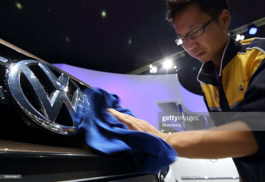 A worker wipes the Volkswagen logo on a vehicle displayed at the FAW Volkswagen booth, the joint venture between Volkswagen AG, and FAW Group Corp., at the Wuhan Motor Show 2013 in Wuhan, China, on Saturday, Oct. 19, 2013. The show will be held through Oct. 23. Photographer: Tomohiro Ohsumi/Bloomberg via Getty Images