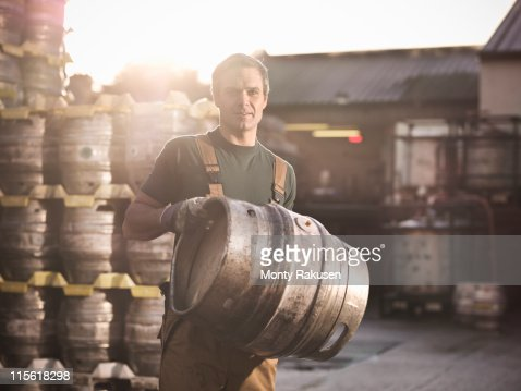 Worker with barrel outside brewery