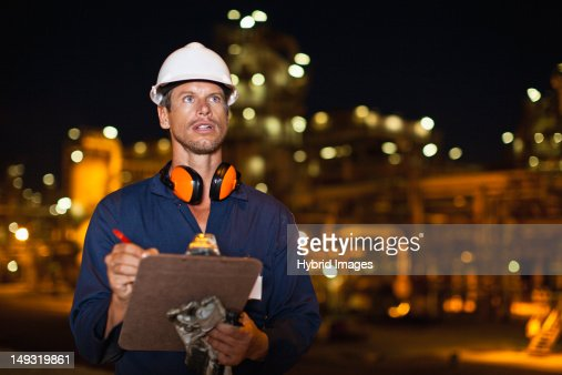 Worker with clipboard at oil refinery