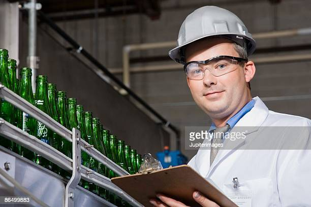 Worker with clipboard by assembly line in brewery