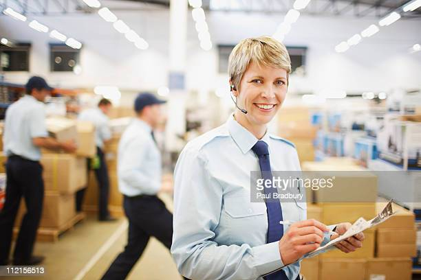 Arbeiter mit Zwischenablage in Versand-Bereich
