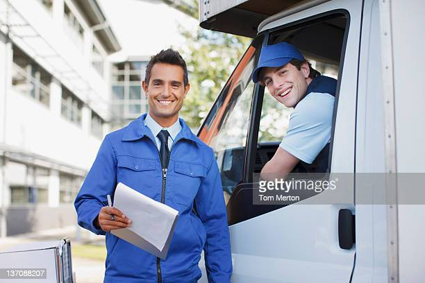 Worker with clipboard standing with truck and driver