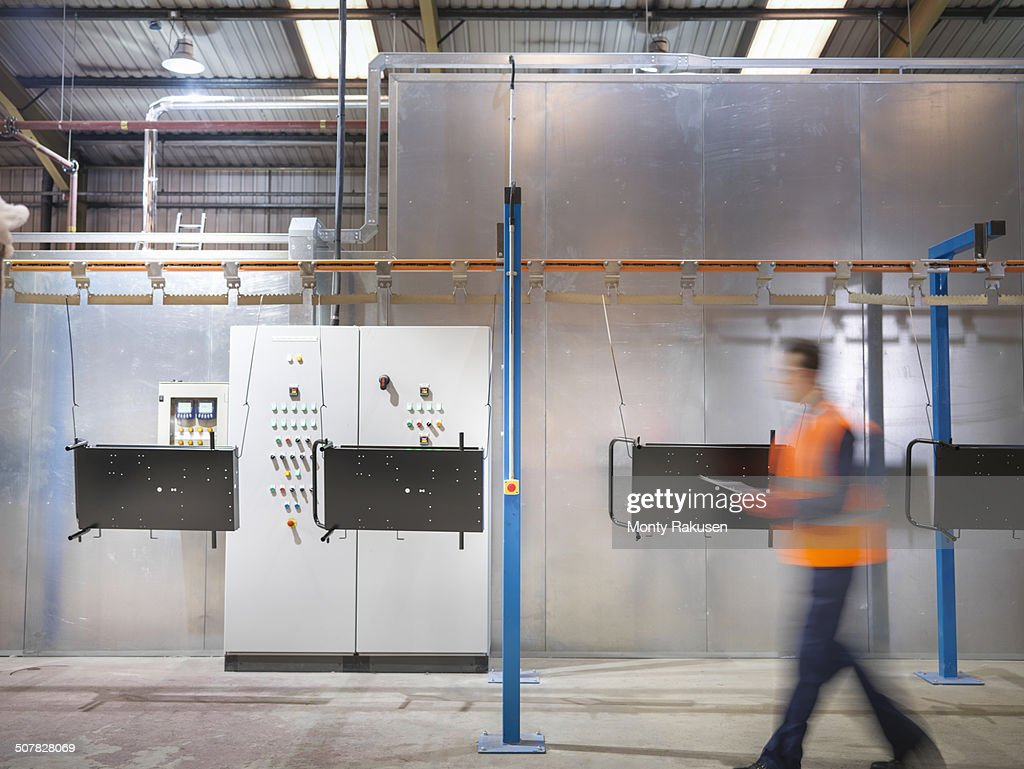 Worker with clipboard walking past paint spray machine in sheet metal factory