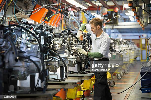 Worker with engines on production line in car factory