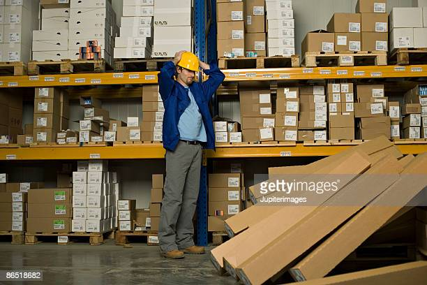 Worker with fallen boxes