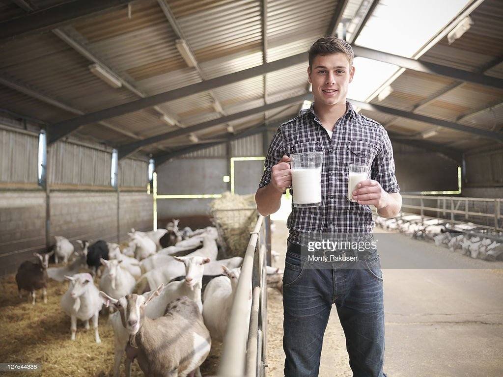 Worker with glass of goats milk on farm