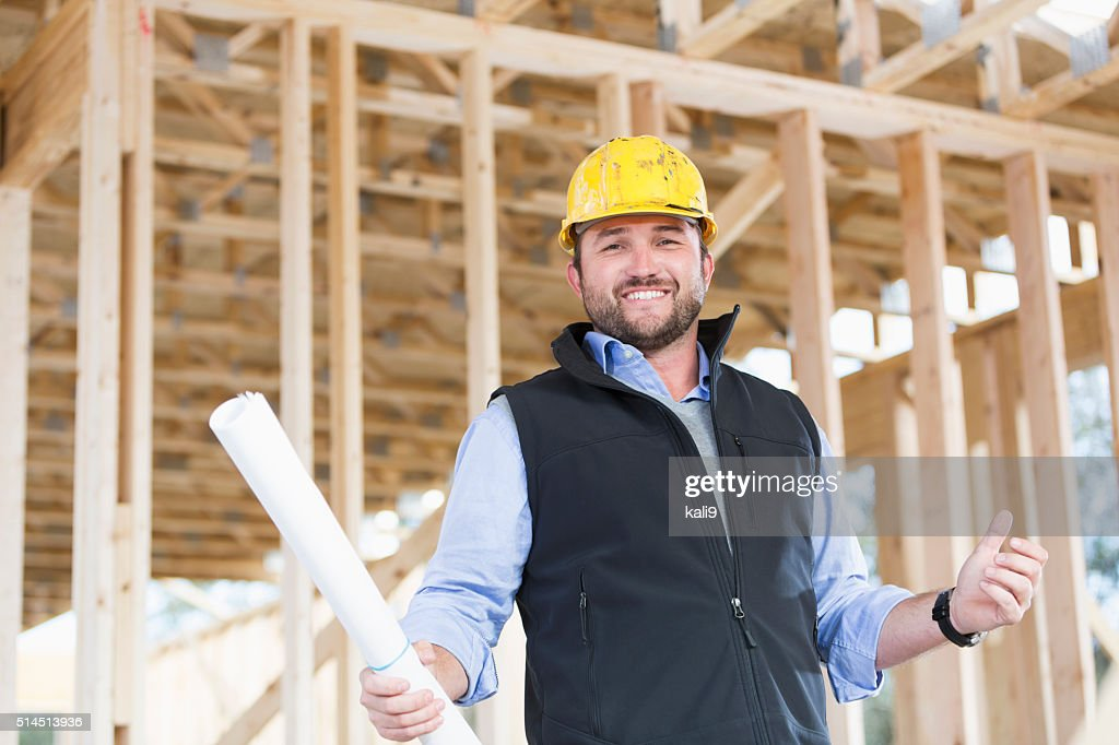 Worker with hardhat and plans at construction site : Stock Photo