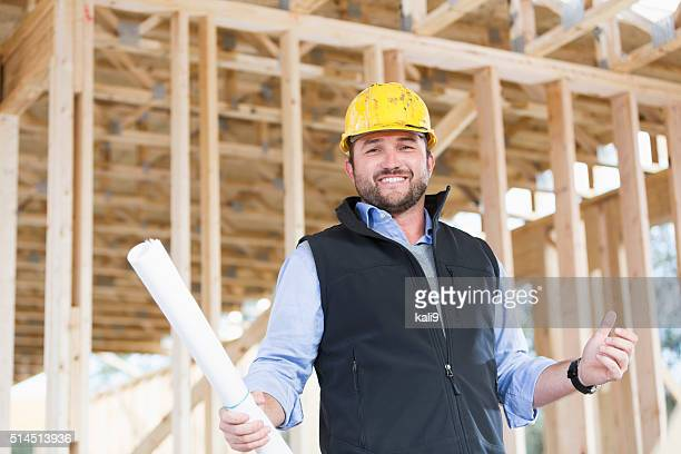 Worker with hardhat and plans at construction site