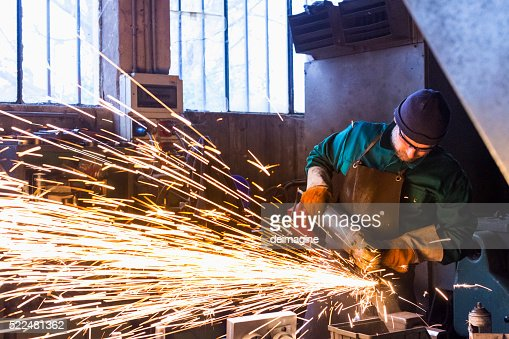 Worker with metal cutting grinder