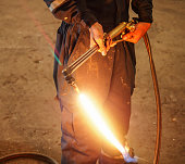Worker with Oxygen Acetylene metal cutting torch in recycle factory, Thailand
