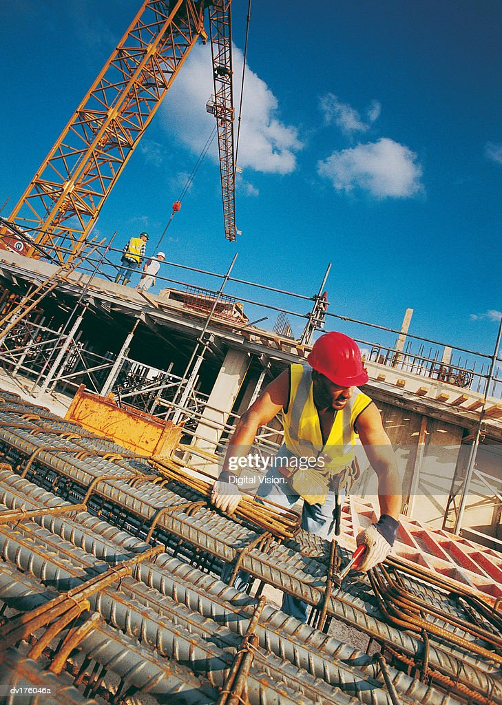 Worker with metal rods, crane and men in background : Stock Photo