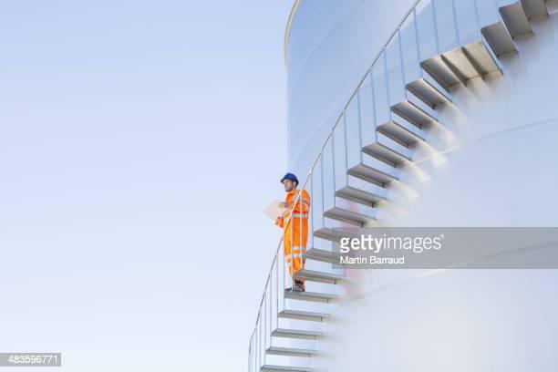 Arbeiter mit Papierkram auf Treppe an silage Stauraum tower