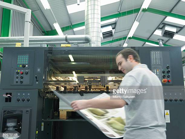 Worker With Plans At Printer