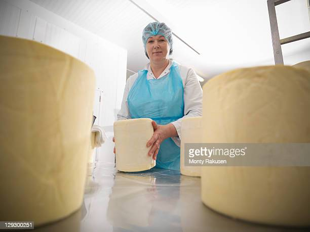 Worker with round cheeses in cheese-making factory