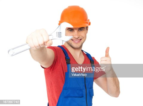 Worker with spanner showing thumbs up sign : Stockfoto