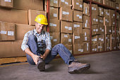Male worker sitting with sprained ankle on the floor in warehouse