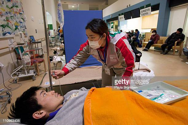 A worker with the Japanese Red Cross takes care of a patient coming from the earthquake shelters at the Ishinomaki hospital March 28 2011 in...