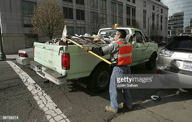 A worker with the Oakland Department of Public Works street cleaning team picks up trash from the street February 6 2006 in Oakland California The...