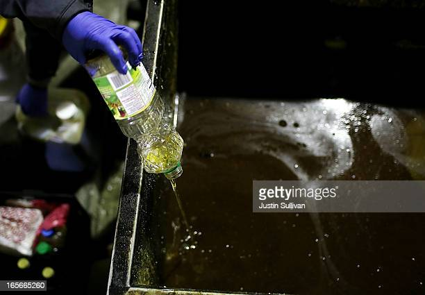 A worker with the San Francisco Water Power and Sewer's SFGreasecycle program dump bottles of used cooking oil into a dumpster on April 5 2013 in San...