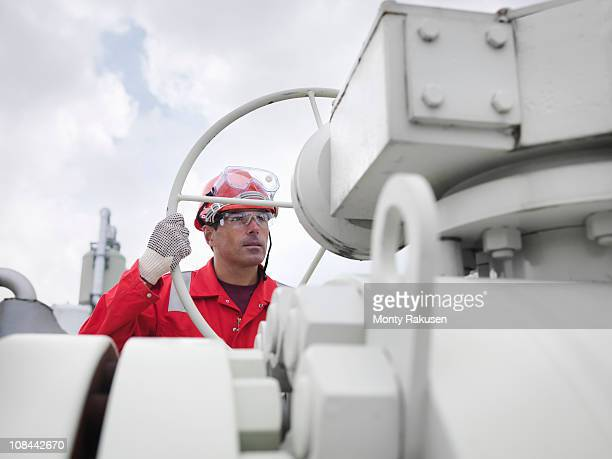 Worker with valve at gas storage plant