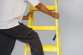 Electrician male rises on the yellow stairs. African builder stand on the wooden stepladder on a gray background. Factory worker with a yellow wooden ladder.