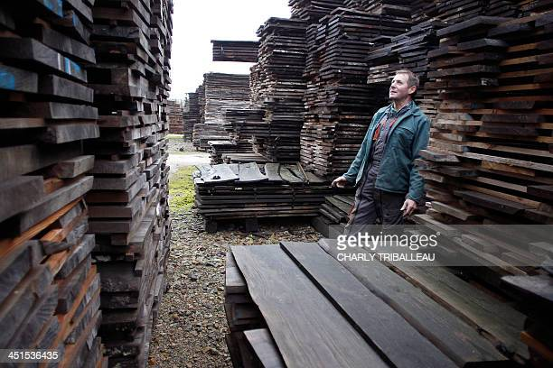 A worker works among piles of logs for firewood on December 21 2012 in Le PinlaGarenne northwestern France The use of wood for heating cheaper than...