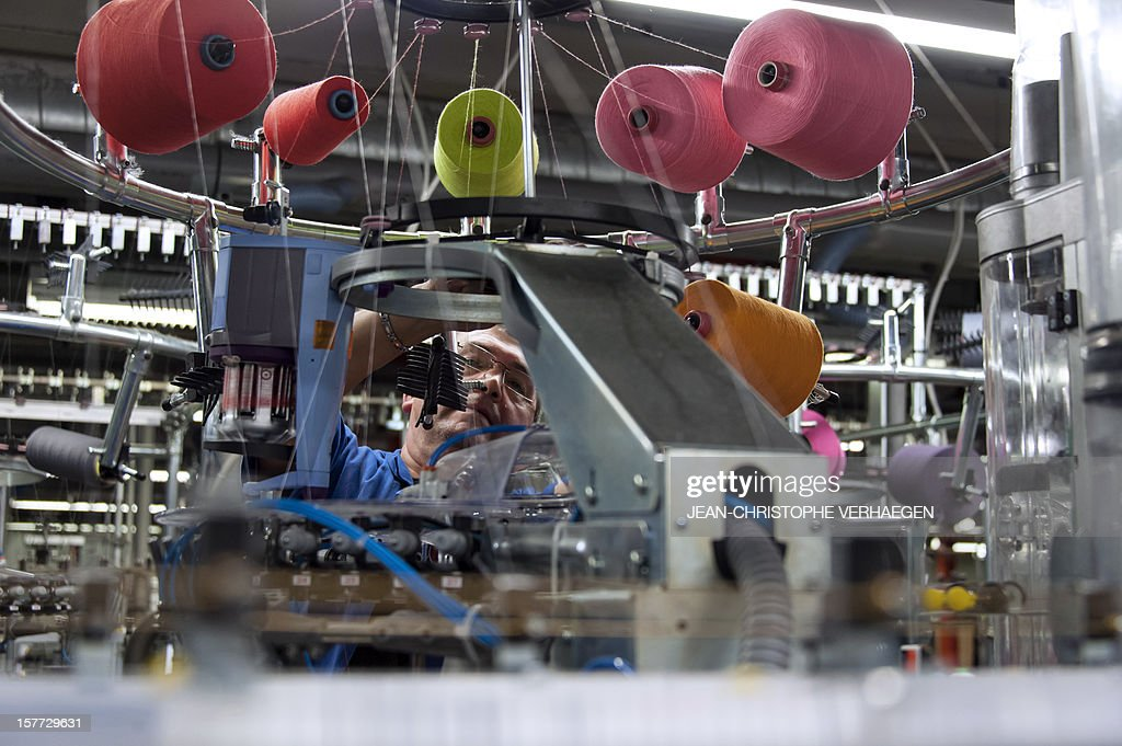 A worker works on a weaving a machine at the production unit of Bleuforet, a Made in France socks, tights, leggings with natural fibers company, in Vagney on December 4, 2012.