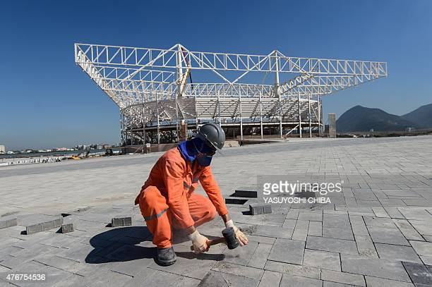 A worker works on the pavement in front of the Aquatic Stadium under construction at the Olympic Park in Rio de Janeiro Brazil on June 11 2015 AFP...