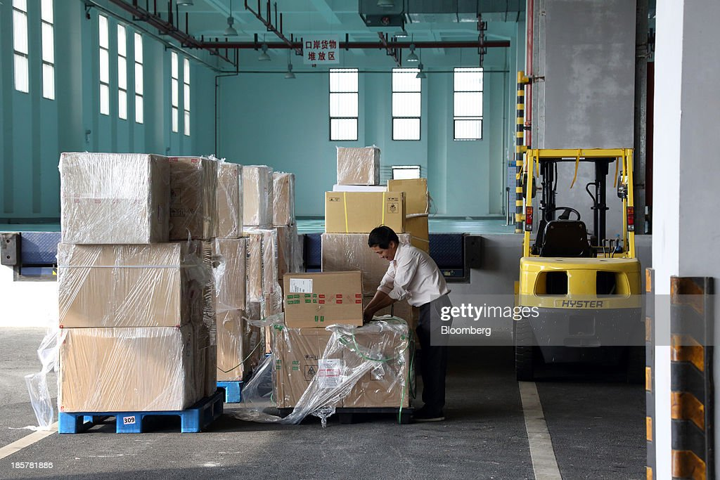 A worker wraps a box in front of a storage area in a logistics center at China (Shanghai) Pilot Free Trade Zone's Pudong free trade zone in Shanghai, China, on Thursday, Oct. 24, 2013. The area is a testing ground for free-market policies that Premier Li Keqiang has signaled he may later implement more broadly in the world's second-largest economy. Photographer: Tomohiro Ohsumi/Bloomberg via Getty Images