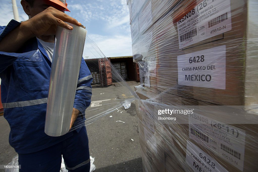 A worker wraps cargo in plastic before it is loaded into a shipping container at the Port of Veracruz in Veracruz, Mexico, on Thursday, Sept. 26 2013. Mexico reported a preliminary trade deficit of $234.2 Million for August, according to the national statistics agency, known as Inegi. Photographer: Susana Gonzalez/Bloomberg via Getty Images
